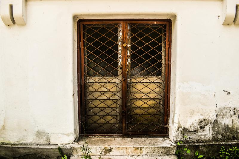 Locked door with iron fence keeping secrets inside the grunge building in the forbidden place stock photo
