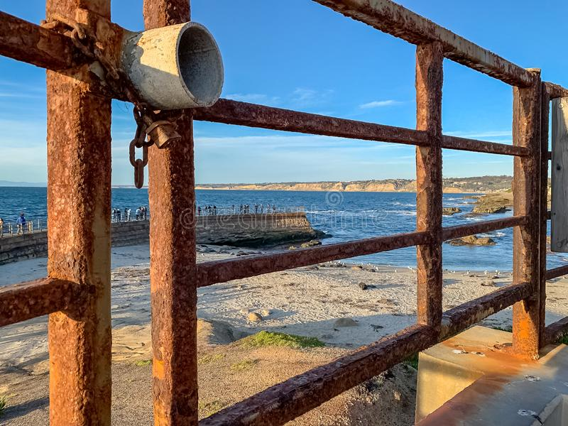 Locked gate in foreground of tourists on pier overlooking La Jolla Beach coves with sea lions royalty free stock images