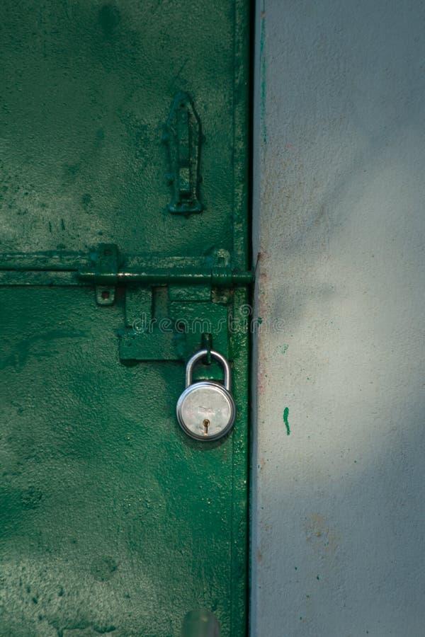 Locked green iron door. White walled building with locked steel door, locked door, old type of door royalty free stock photos