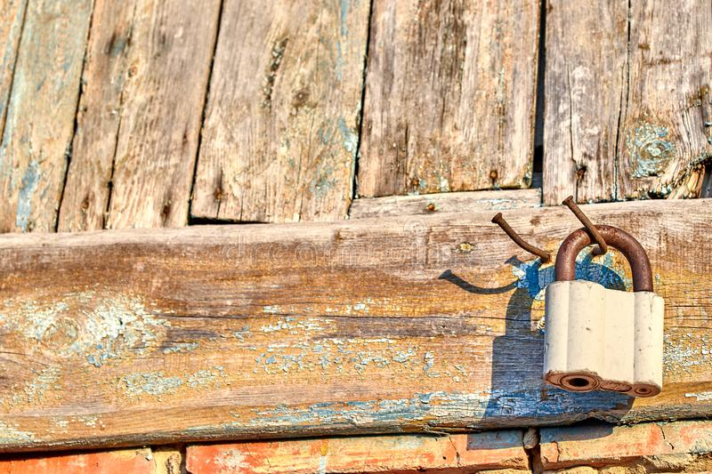 Locked old castle on a nail on the background of old texture boards royalty free stock images