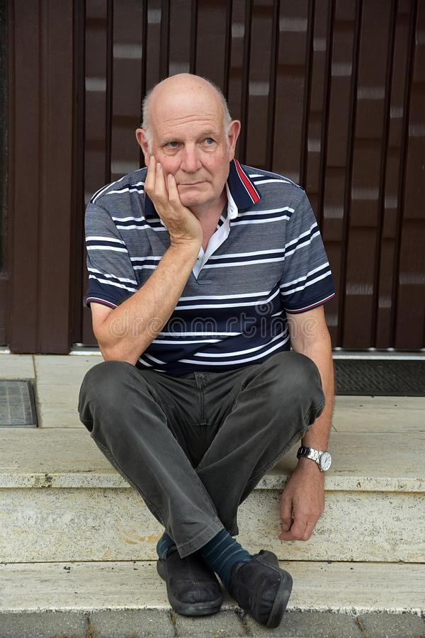 Locked out senior man sitting in front of his house stock image