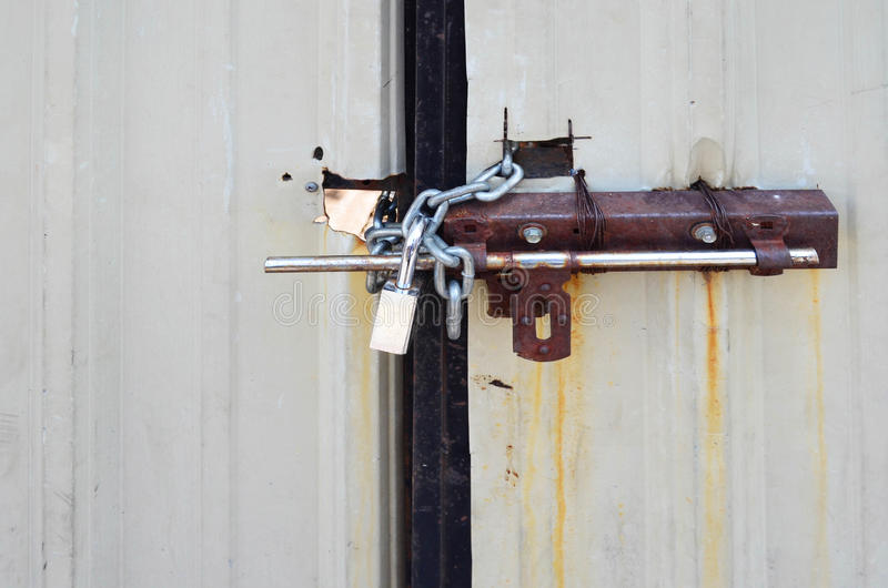 Locked padlock and chained on galvanize metal sheet door stock photography