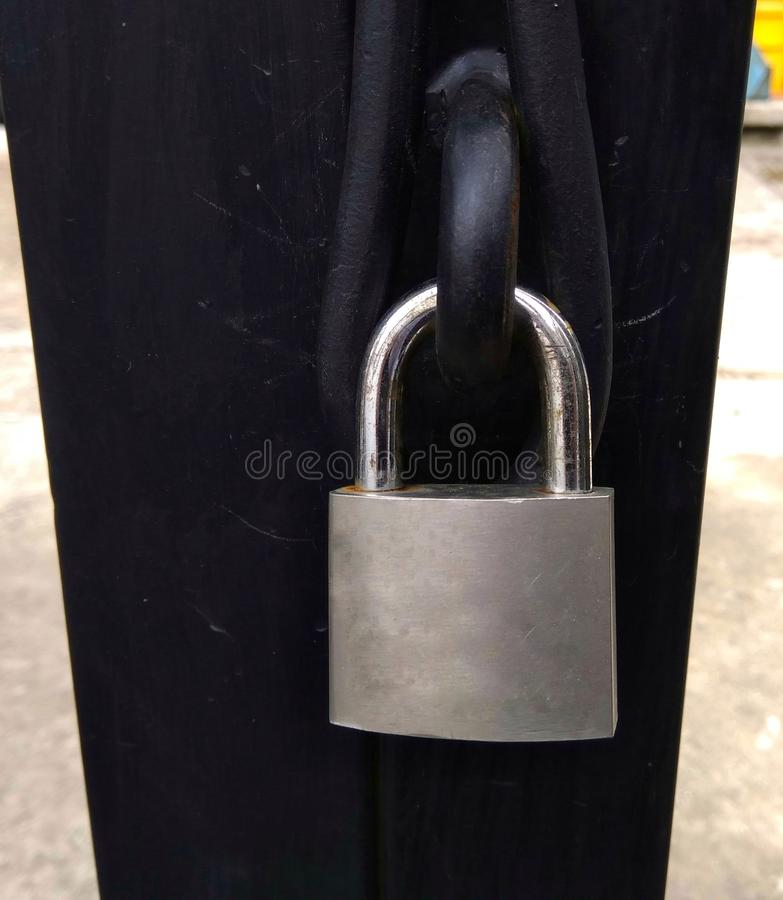 Locked padlock on a gate at house stock image