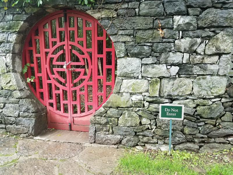Locked red door at Chinese garden with do not enter sign. And stone wall stock photo