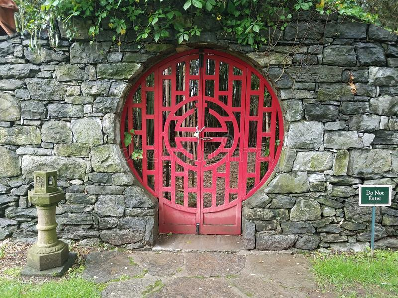 Locked red door at Chinese garden with do not enter sign. And stone wall royalty free stock photography