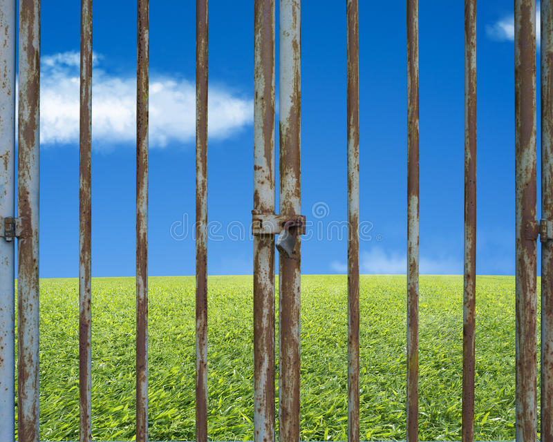 Locked rusty door with beautiful landscape, green meadow blue sk stock photo