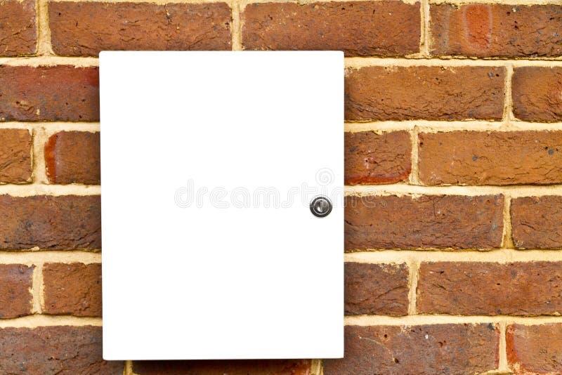 Locked white cupboard on a brick wall