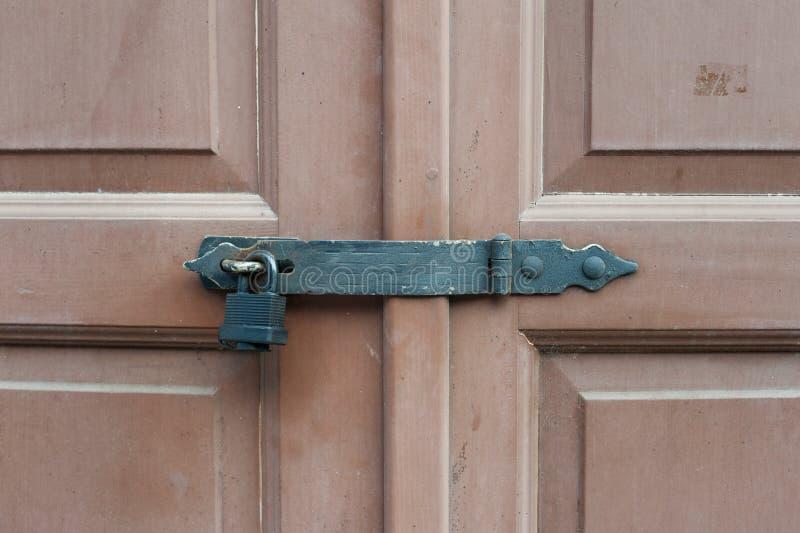 Locked wooden doors with black metal lock stock photo