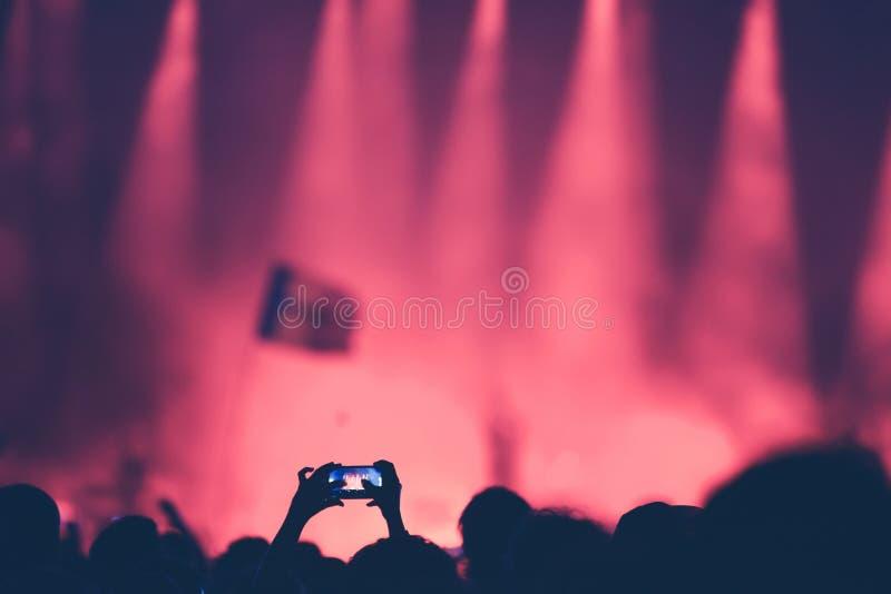 Lockern Sie das Machen des Fotos des Konzerts mit einem intelligenten Telefon auf stockbilder