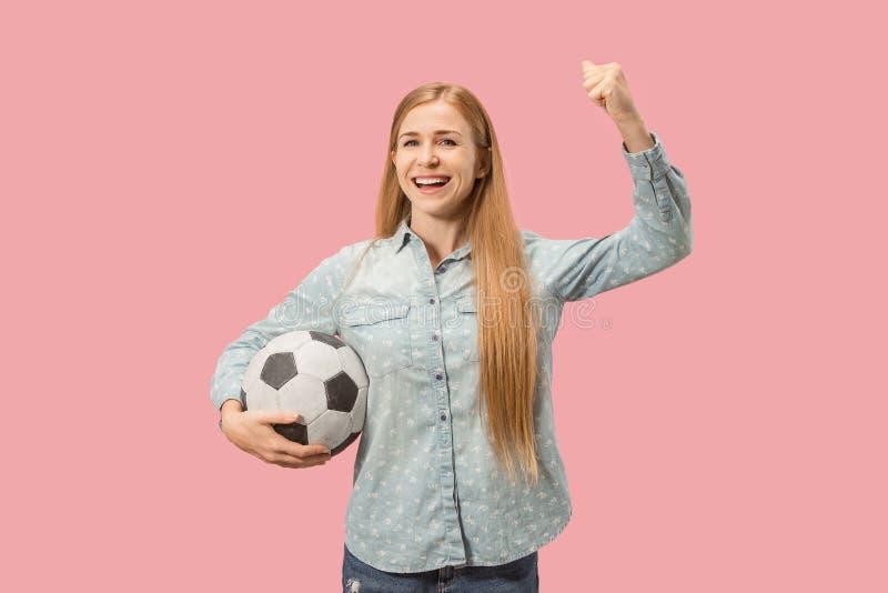 Lockern Sie den Sportfrauenspieler auf, der Fußball lokalisiert auf rosa Hintergrund hält stockfotos