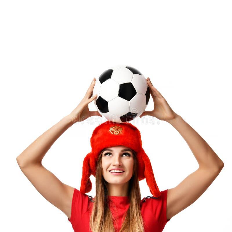 Lockern Sie Sportfrauenspieler in der roten Uniform und im russischen Winterhutgrifffußballfeiern auf lizenzfreie stockbilder
