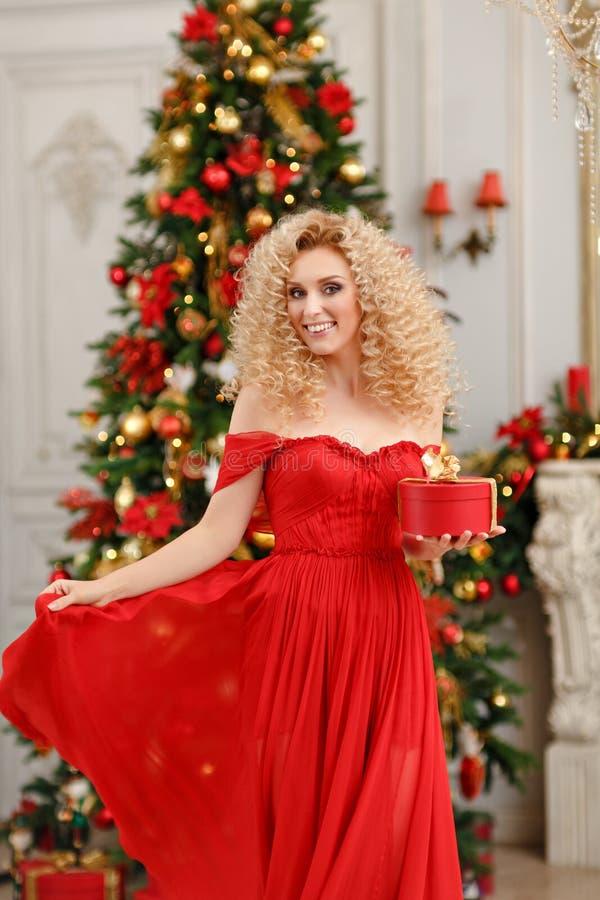 Lockig blond flicka i en röd klänning som rymmer en gåva och dansar i C royaltyfria foton