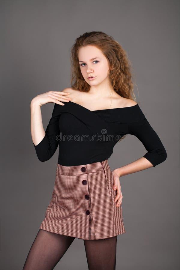 Lockig blondin för stående i en svart blus och en kort kjol, på den gråa studioväggen royaltyfri bild