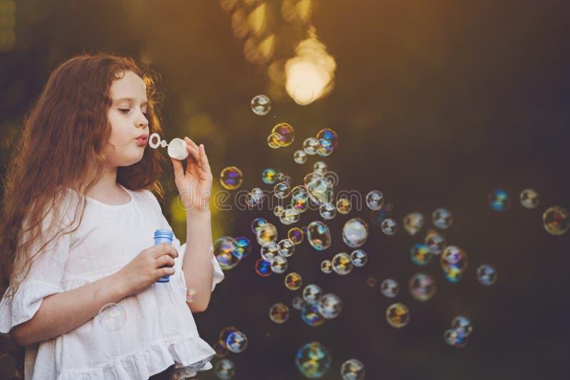 Lockig flicka som blåser såpbubblor royaltyfri foto