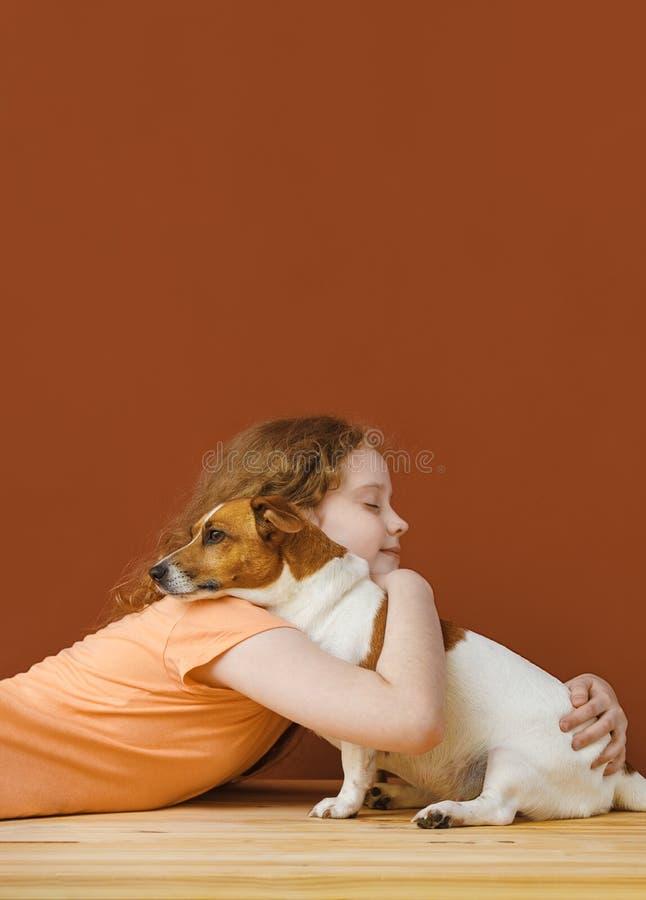 Lockig flicka som omfamnar hennes vänhund royaltyfria foton