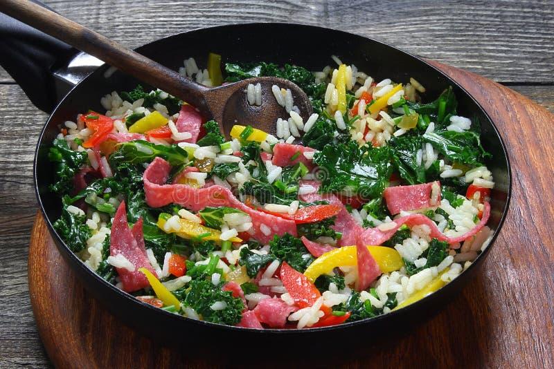 Lockig grönkål med ris och salami arkivfoton
