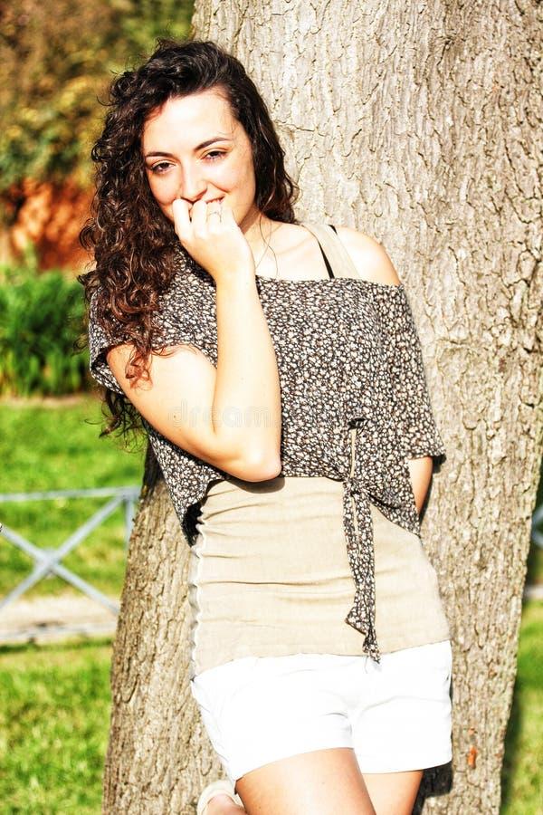 Lockig härlig blyg ung flicka med trevligt leende royaltyfri foto
