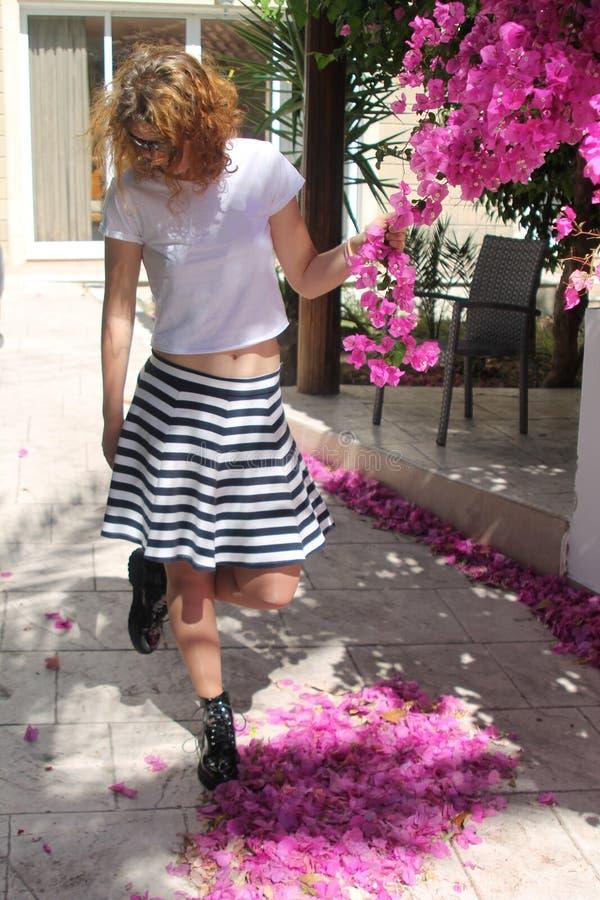 Lockig haired flicka med rosa blommor royaltyfria foton