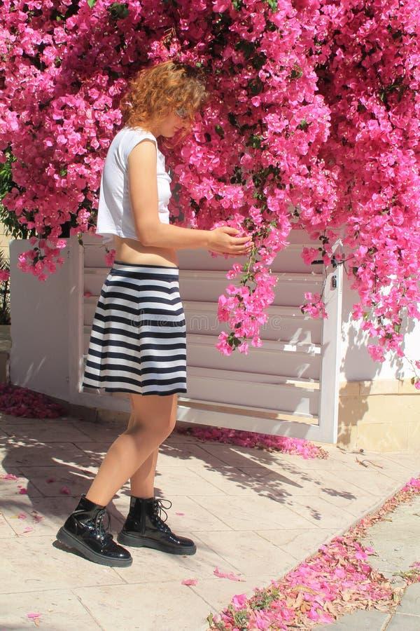 Lockig haired flicka med rosa blommor royaltyfria bilder