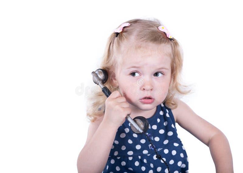 Lockig-haired liten flicka med en tappningtelefon arkivbilder