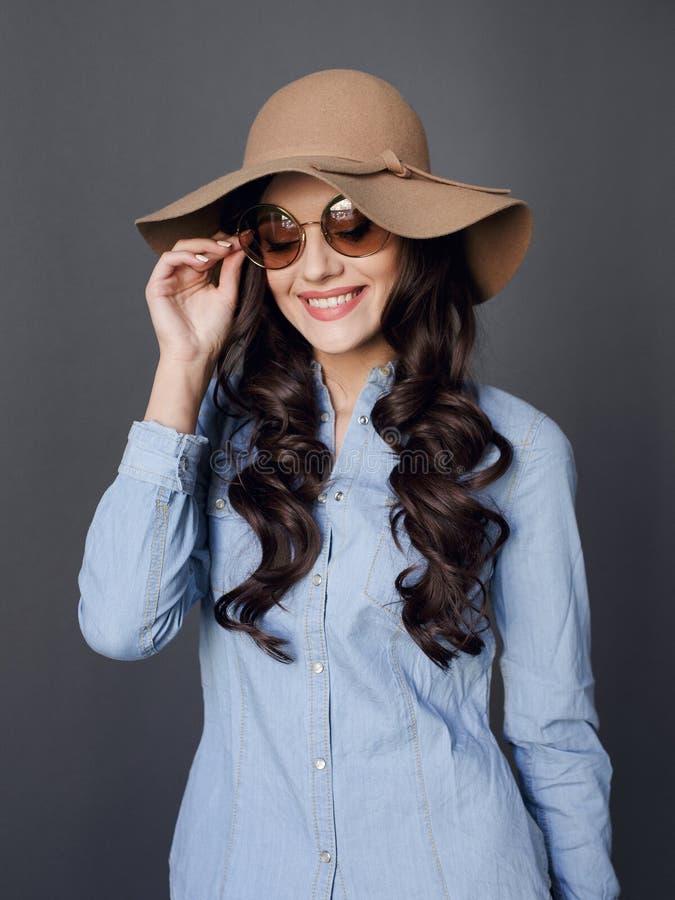 Lockig haired lycklig brunettmodell, elegant iklädd hatt och rund solglasögon, på en grå bakgrund arkivbild