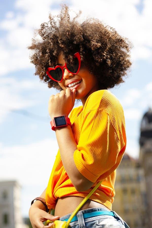 Lockig kvinna för upptakt som bär hjärta-formad solglasögon arkivbild