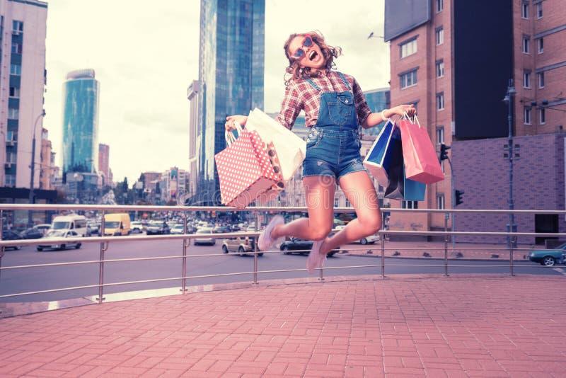 Lockig kvinna som bär röd solglasögon och vita gymnastikskor som högt hoppar fotografering för bildbyråer