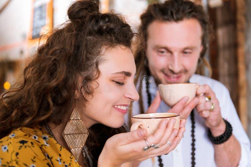 Lockig lockande kvinna som luktar smak av trevligt te royaltyfri foto