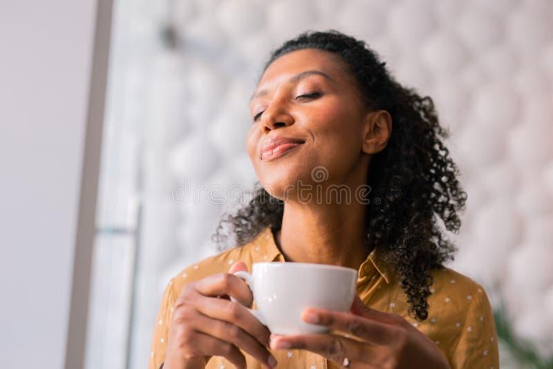 Lockig mörker-haired lockande kvinna som känner sig glad, medan dricka kaffe arkivfoto