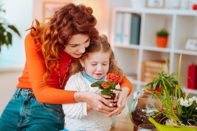Lockig mamma och gullig dotter som tillsammans rymmer trevliga röda blommor arkivfoto