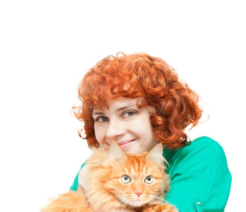 Lockig rödhårig flicka med en isolerad röd katt royaltyfri fotografi