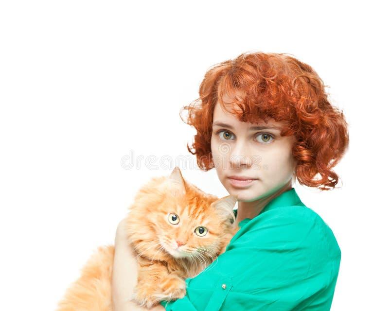Lockig rödhårig flicka med en isolerad röd katt fotografering för bildbyråer