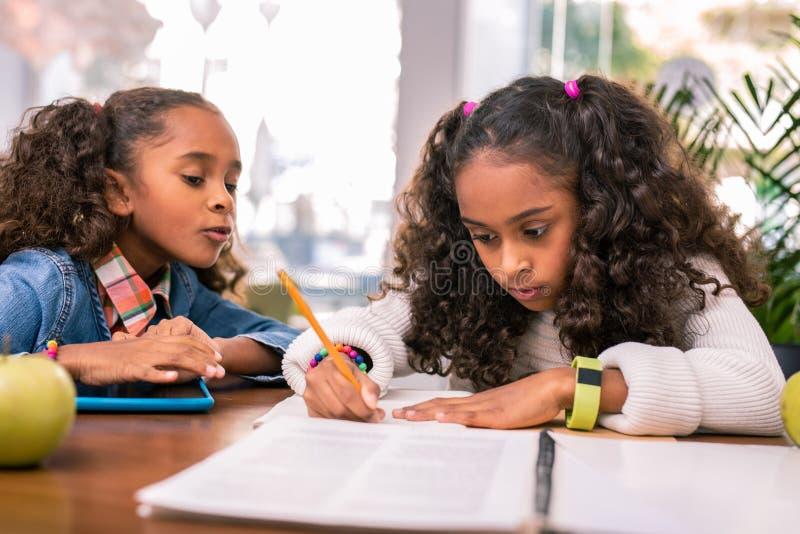 Lockig skolflicka som bär den gula smarta klockan som gör hennes läxa royaltyfri bild