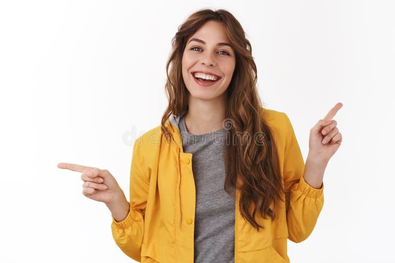 Lockig stilfull frisyr för entusiastisk enfaldig lockig-haired härlig ung flicka som pekar pekfingrar åt sidan som rätt lämnas royaltyfri fotografi