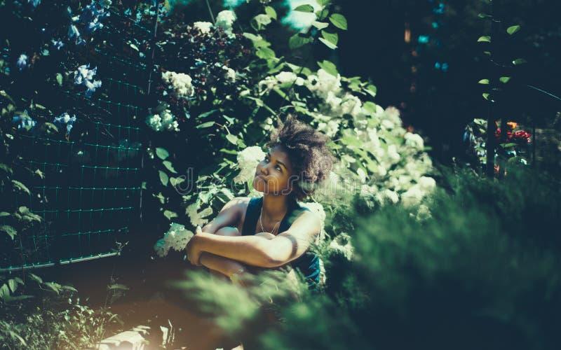 Lockig svart afro amerikansk flicka i sommarträdgård arkivbilder