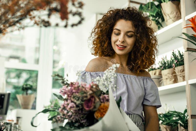 Lockig tillfredsställd blomsterhandlarekänsla, medan se den trevliga perfekta buketten arkivbilder