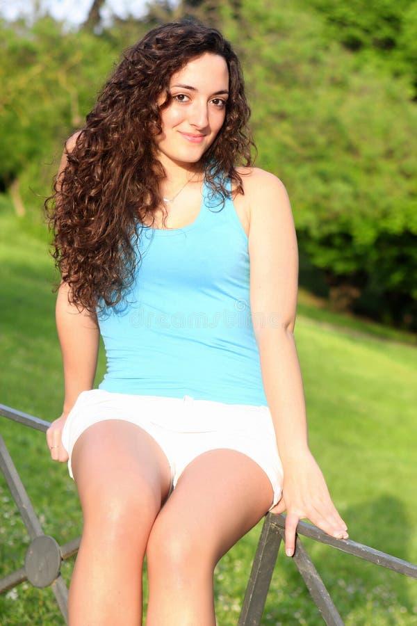 Lockig tonårig flicka som ler i en parkera fotografering för bildbyråer