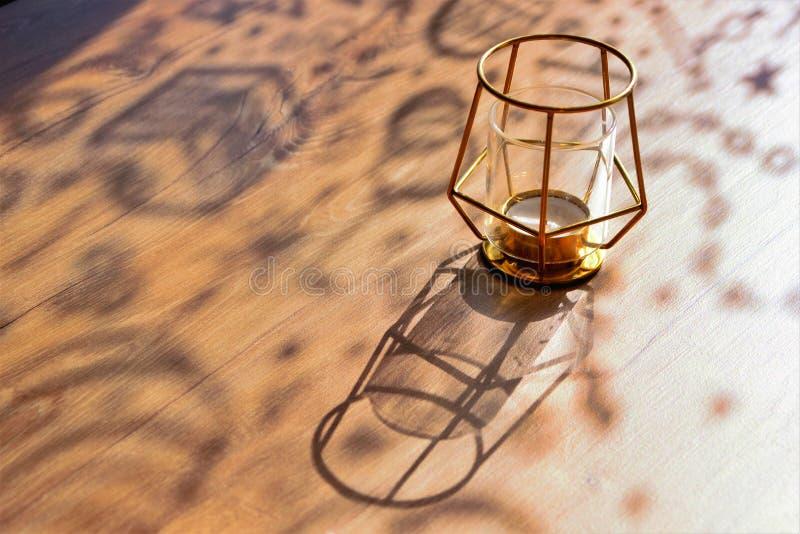 Lockiga skuggor på en trätabell på en solig dag, märkes- ljusstake, närbild, selektiv fokus, kopieringsutrymme arkivbilder