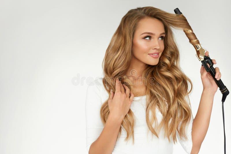 Lockiges Haar Schönheit, die langes gewelltes Haar mit Eisen kräuselt stockbilder