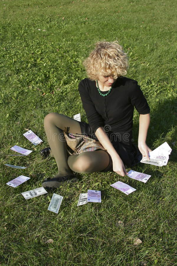 Lockiges Mädchen mit Geld lizenzfreies stockfoto