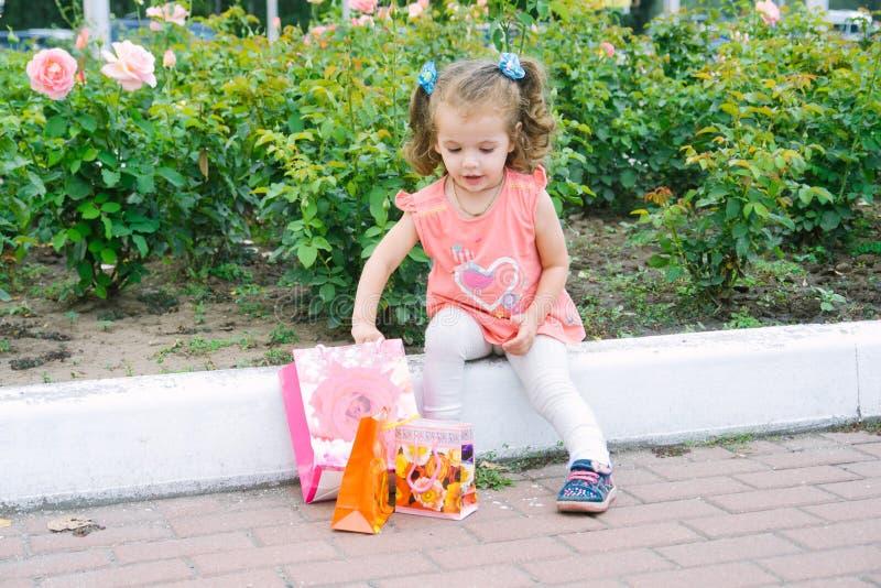 Lockigt hår för förtjusande liten flicka med färgrika shoppingpåsar arkivbild