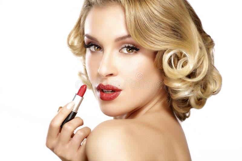 Lockigt hår för härlig ung blond modell som applicerar läppstift royaltyfria foton