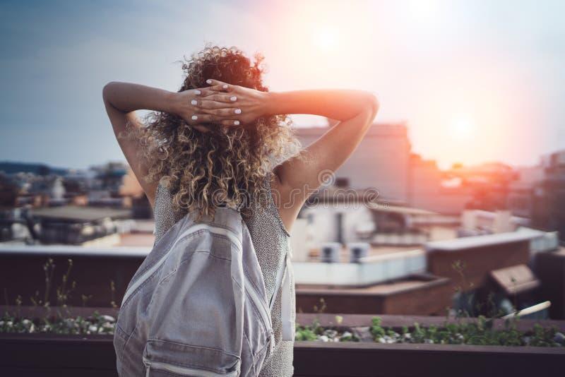 Lockigt hår Hansome för ung kvinna och tillfälliga kläder som enjoing den härliga sikten av staden på solnedgång fotografering för bildbyråer