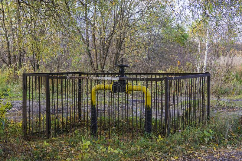 The locking device of the gas pipeline passing in the wood and brought outside, protected by a fence for safety. Moscow region, Ru. Ssia. 2017 stock photography