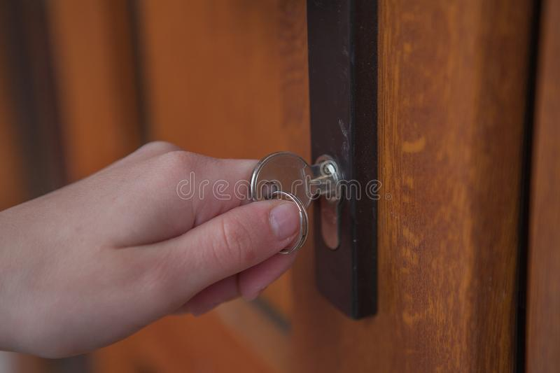 Locking up or unlocking door with key in hand.  royalty free stock photography