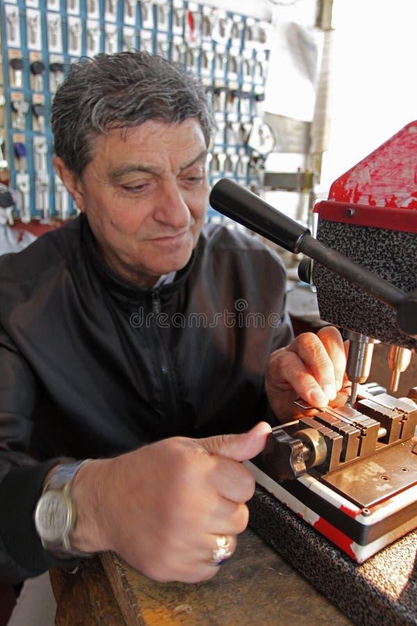 Locksmith в мастерской делает новый ключ Профессиональный делая ключ в locksmith Персона которая делает и ремонтирует ключи и зам стоковая фотография rf