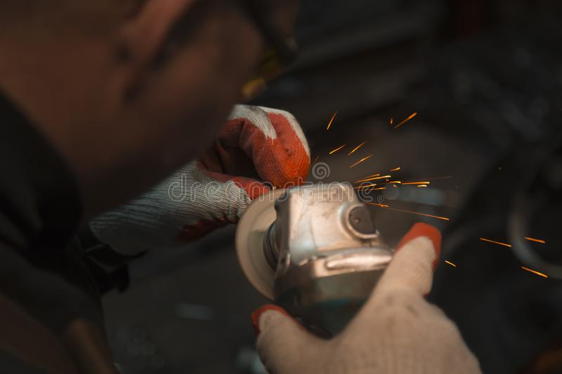 Locksmith man in gloves and yellow glasses at work. A man sharpens a drill with a grinding machine with gloves and yellow glasses royalty free stock images