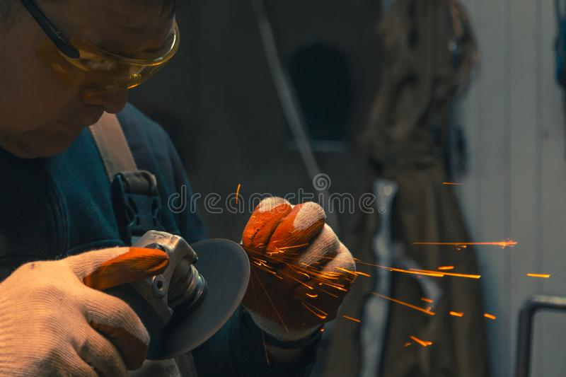 Locksmith man in gloves and yellow glasses at work. A man sharpens a drill with a grinding machine with gloves and yellow glasses stock photo