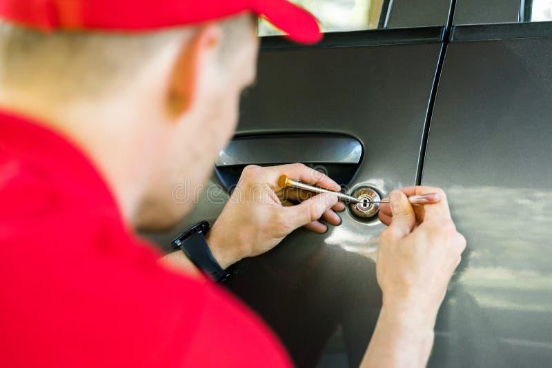 Locksmith opening car door with lockpicker stock photo