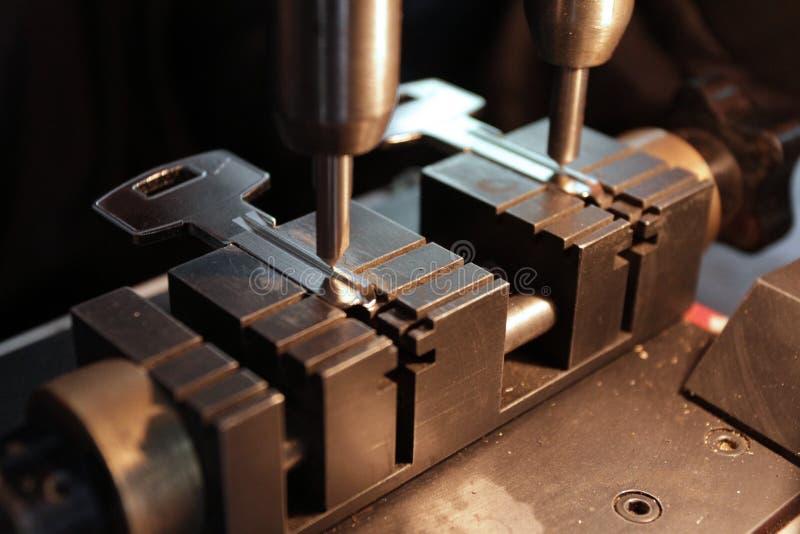 Locksmith w warsztacie robi nowemu kluczowi Fachowy robi klucz w locksmith Osoba która robi kędziorkom i naprawia klucze i Kluczo zdjęcie stock